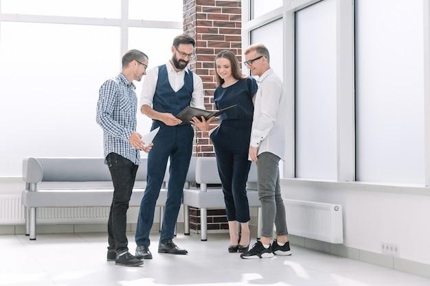 オフィスロビーに立って、新しいアイデアを議論するビジネスチーム