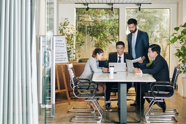 회의에서 개발 전략을 논의하고 아이디어를 공유하고 보고서를 확인하는 비즈니스 팀