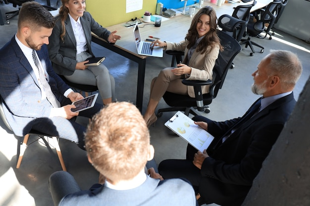 Business team discussing together business plans in office.
