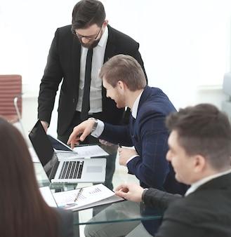 현대 사무실의 책상에서 업무 문제를 논의하는 비즈니스 팀