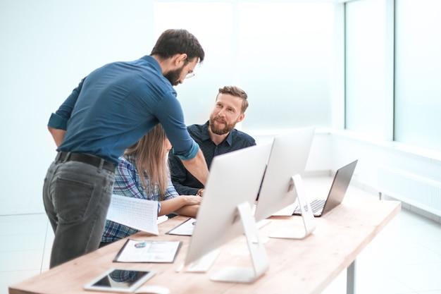 ライトオフィスで作業文書について話し合うビジネスチーム。コピースペースのある写真