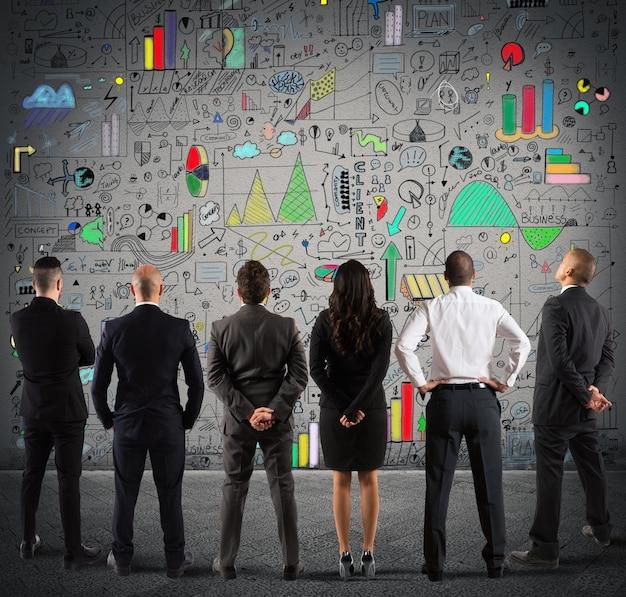 壁に新しい複雑なプロジェクトを描くビジネスチーム