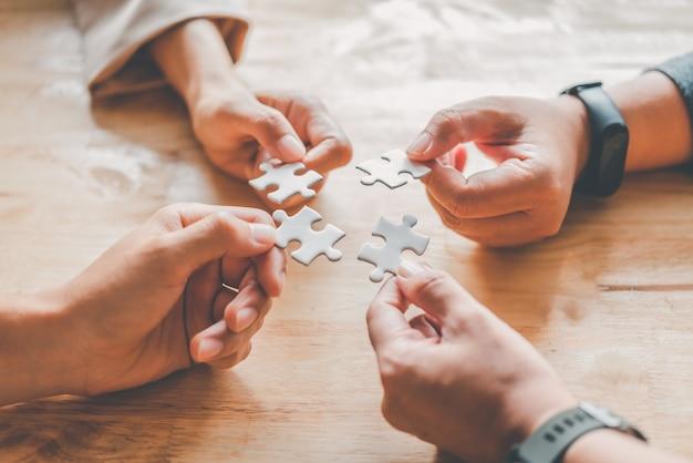 Бизнес-команда решает белые головоломки, которые вот-вот упадут, чтобы получить полный рабочий лист - попытка добиться успеха.