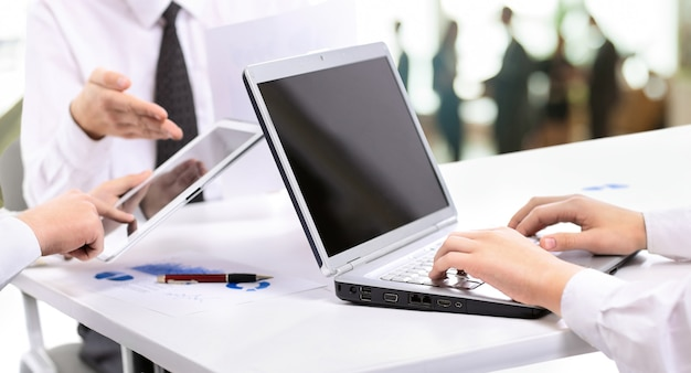 Business team handles financial charts on laptop and tablet