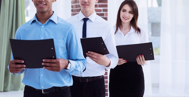 사무실에 서 있는 계약서 사본을 들고 있는 비즈니스 팀.