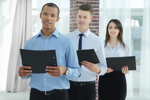 사무실에 서있는 계약의 복사본을 들고 비즈니스 팀.
