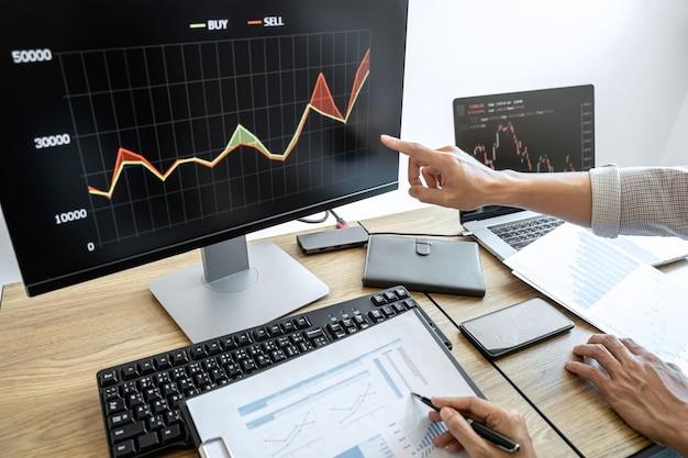 コンピューターを使用したビジネスチームの投資、グラフ株式市場取引の計画と分析