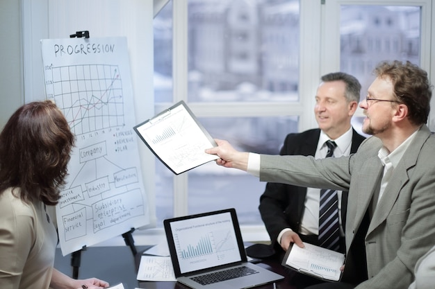 Business team and investors discussing the company's profit in a modern office