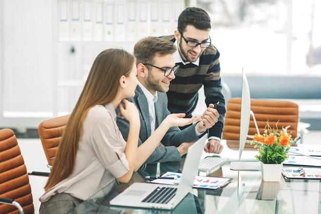 비즈니스 팀은 현대적인 사무실의 책상 뒤에 앉아 새로운 프로젝트를 개발하고 있습니다.