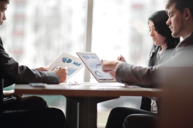 ビジネスチームは、コピースペースで財務スケジュールの写真について話し合っています