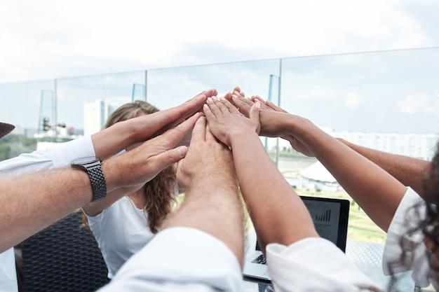 비즈니스 팀이 데스크톱을 통해 손을 잡고 있습니다.