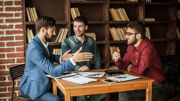 비즈니스 팀은 현대 사무실의 직장에서 재정 일정을 다루고 있습니다.