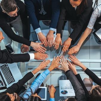デスクトップ上で輪になって手を組むビジネスチーム