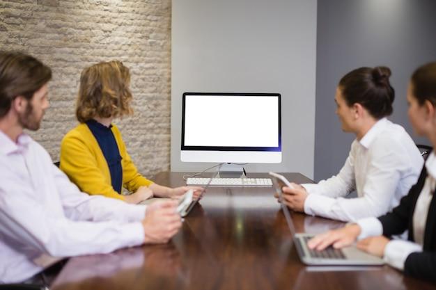 会議室のコンピューター画面を見て事業チーム