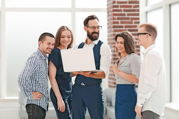 オフィスのロビーに立っているノートパソコンの画面を見ているビジネスチーム