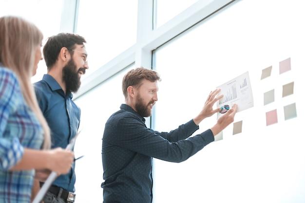 Бизнес-группа, глядя на финансовую диаграмму на стеклянной доске