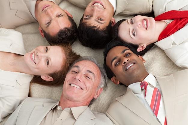一緒に頭を持つ床に横たわるビジネスチーム