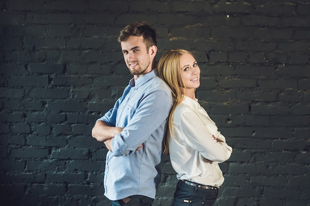 暗い表面に立っている若いビジネスマンで構成されたビジネスチームの男性と女性。