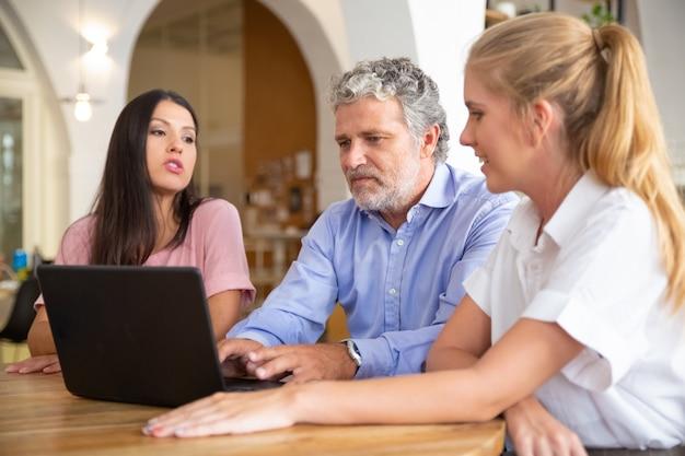 Деловая команда из трех человек сидит за ноутбуком, смотрит и обсуждает контент