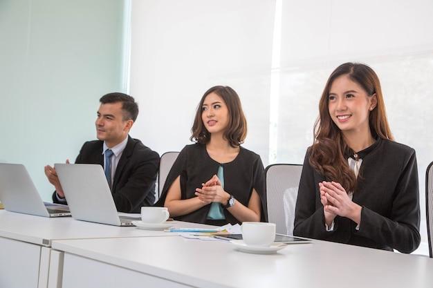 Люди бизнес-команды аплодируют руками своей целью в конференц-зале.