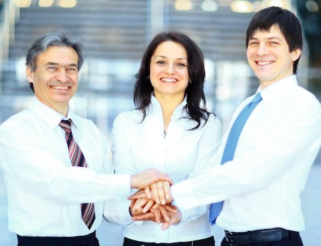 お互いの上に手を重ねるビジネスチーム