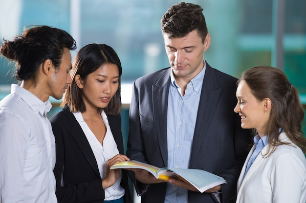 Business team reading book together Free Photo