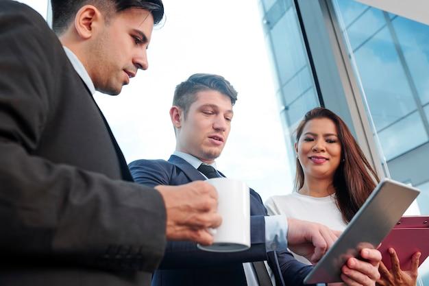 Бизнес-группа, читающая данные на планшете