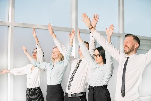 手を挙げて成功を示しているビジネスチーム。成功するチームワークの概念