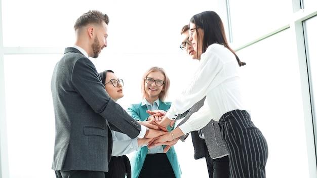 オフィスに立っている間、彼らの団結を示すビジネスチーム。チームワークの概念