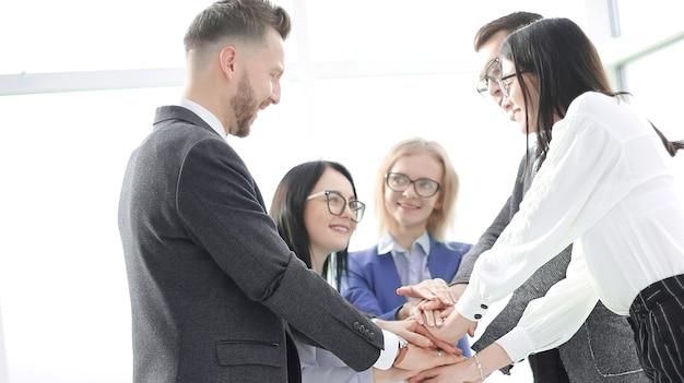 Деловая команда показывает свое единство, стоя в офисе. концепция совместной работы
