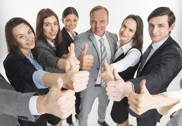 Деловая команда показывает палец вверх, изолированные на белой стене