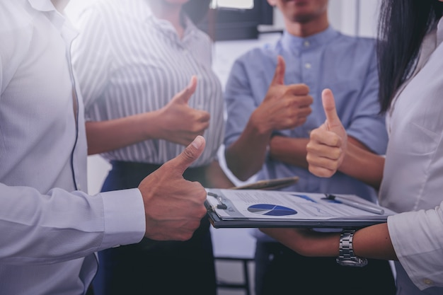 Business team showing thumbs up as like sign. close up hand.