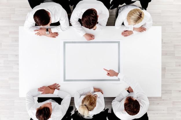 白いテーブル、白いコピースペースの周りに座っているビジネスチーム