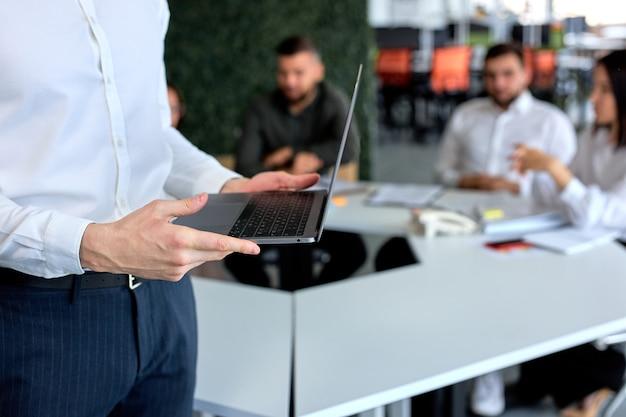 ビジネスマンがスピーチをする準備をしている間、現代の明るいオフィスに座っているビジネスチーム