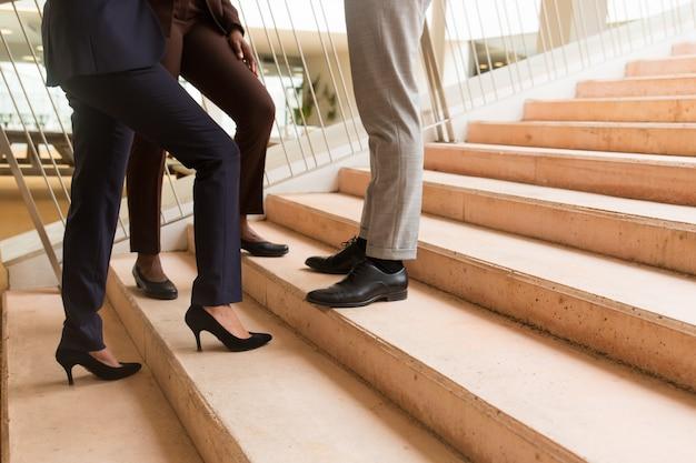 Бизнес-команда стоит на лестнице в помещении