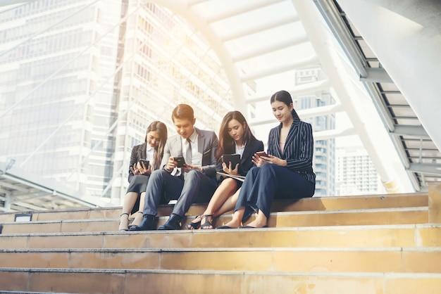 비즈니스 팀은 스마트 폰을 사용하여 발걸음을 내딛습니다.