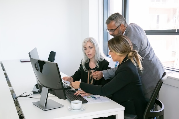 Business team of three analyzing reports, sitting at workplace with monitors together, holding, reviewing and discussing papers with charts. copy space. inclusive workplace concept