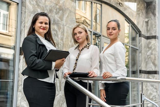 ビジネスチーム。建物の外でポーズをとるフォルダーとタブレットとスーツの3人の女性