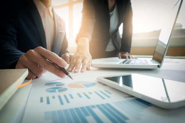 ビジネスチームの2つの同僚は、新しい計画の金融グラフのデータを議論するオフィスのテーブル