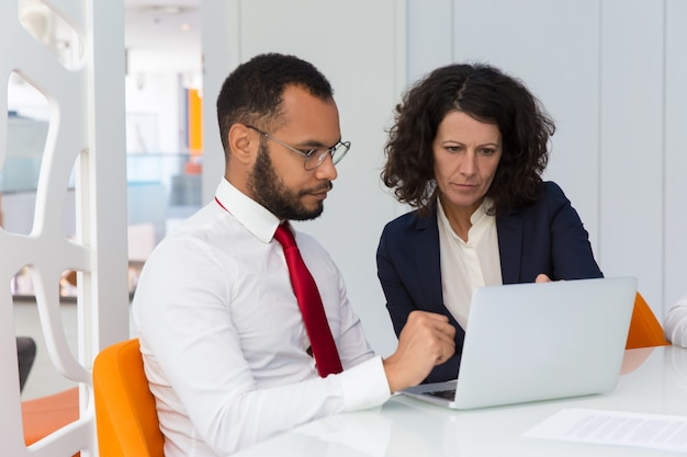 Business team of two using computer together