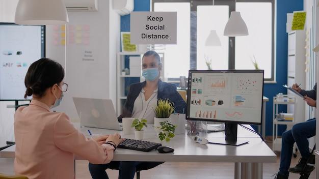 ラップトップで財務戦略を入力し、オフィスの机に座っているときにcovid19の感染を防ぐためにフェイスマスクを着用しているビジネスチーム。ウイルス病を回避するために社会的距離を保つ同僚