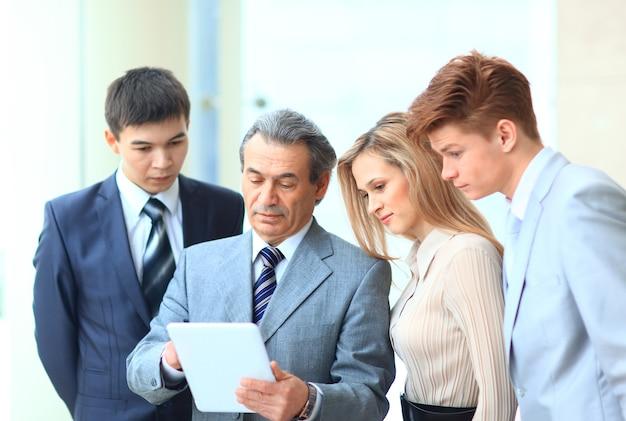디지털 태블릿을 사용하여 새로운 정보를 보는 비즈니스 팀