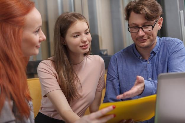 현대적인 작업 공간에서 회의 중에 노트북을 사용하는 비즈니스 팀