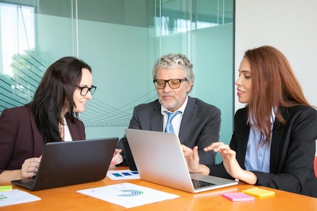 テーブルで企業の会議で図を分析しながらコンピューターを使用してビジネスチーム。