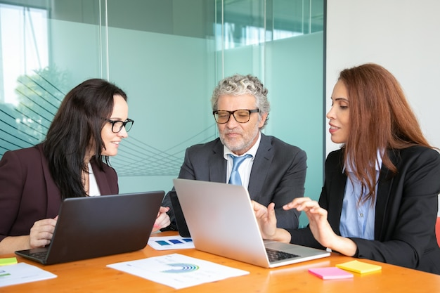 Business team using computers while analyzing diagram at corporate meeting at table.