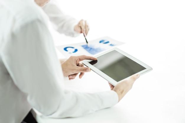 디지털 태블릿을 사용하는 비즈니스 팀, 보고서는 데스크 뒤의 마케팅을 분석합니다.