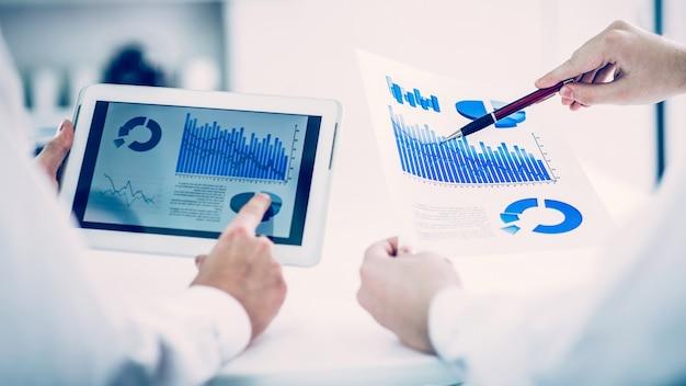 デジタルタブレットを使用し、会社の開発の財務スケジュールを処理するビジネスチーム