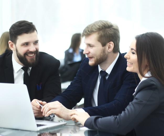 Бизнес-группа, использующая ноутбук для работы в офисе
