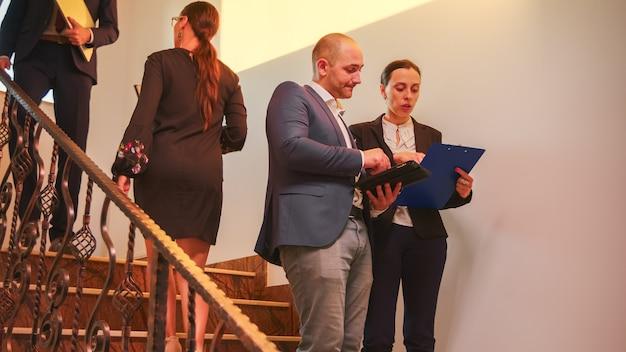 タブレットを使用して作業している同僚と会う階段を歩いているビジネスチーム、ビジネスビルの階段で企業のエグゼクティブマネージャーと話している女性。オフィスの階段で働き過ぎの起業家。