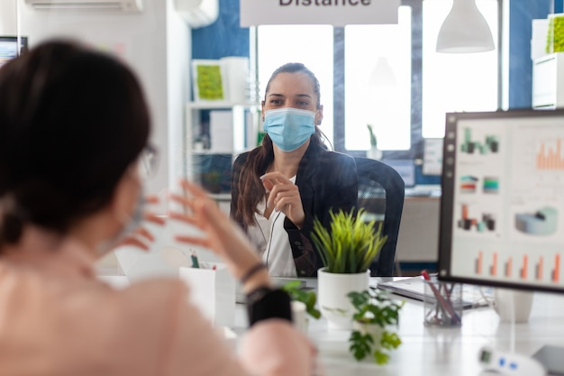 Business team wearing medical face mask to prevent infection with coronavirus during global pandemic discussing company strategy in startup office. coworkers planning management presentation